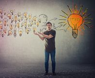Casual young man, confused face expression, holding hands outstretched as receiving a lot of ideas gathering and create a stock image