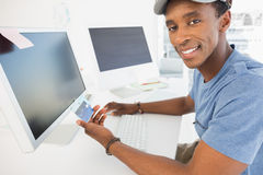 Casual young man doing online shopping in office Stock Photography