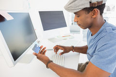 Casual young man doing online shopping in office Stock Image