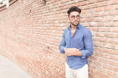 Casual young man fixing his sleeve near brick wall Royalty Free Stock Images