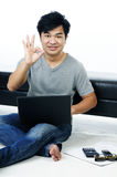Casual young man giving OK sign and using laptop Royalty Free Stock Photo