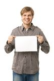 Casual young man holding blank sheet. Of paper, smiling. Isolated on white Stock Images