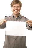 Casual young man holding blank sheet. Of paper, smiling. Isolated on white, selective focus on paper Stock Photo