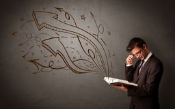 Young man holding book with arrows Stock Image
