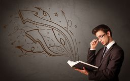 Young man holding book with arrows royalty free stock photography