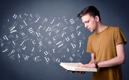 Young man holding book with letters Royalty Free Stock Photography