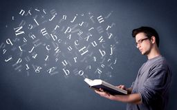 Young man holding book with letters Royalty Free Stock Photo
