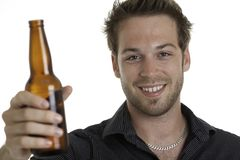 Casual young man holding bottle of beer, smiling Royalty Free Stock Image