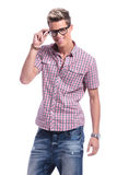 Casual young man holding eyeglasses Royalty Free Stock Image