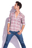 Man with hands in pockets looks away. Casual young man holding his thumbs in his pockets with his legs spread and looking up and to a side, away from the camera Stock Photos