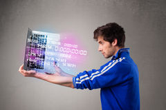 Casual man holding laptop with exploding data and numbers Stock Photography