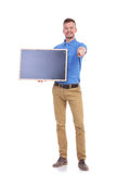 Casual young man holds blackboard and points at you Stock Photo