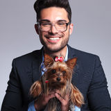 Casual young man holds cute puppy Royalty Free Stock Photo