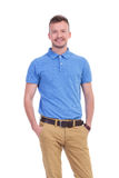 Casual young man holds hands in pockets. Picture of a young casual man with his hands in his pockets, smiling for the camera. isolated on a white background Stock Photography