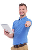 Casual young man holds his tablet and points. Picture of a young casual man holding a tablet while pointing and smiling for the camera. isolated on a white Royalty Free Stock Photo