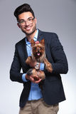 Casual young man holds puppy in both hands Royalty Free Stock Photography