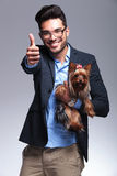 Casual young man holds puppy and shows thumb up Stock Photography
