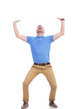 Casual young man holds something imaginary. Full length picture of a young casual man holding something imaginary above him with both hands and screaming out of Royalty Free Stock Image