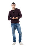 Casual young man in jeans holding mobile phone looking at camera. Full body length portrait isolated over white studio background Royalty Free Stock Photo