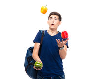 Casual young man juggles with pepper Stock Image