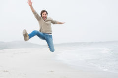 Casual young man jumping at beach Royalty Free Stock Images