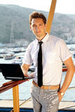 Casual young man with laptop,  standing Royalty Free Stock Images