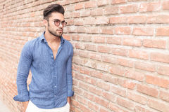 Casual young man leaning against brick wall Royalty Free Stock Photography