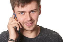 Casual young man with light beard, listening on mobile phone, is Stock Photo