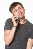 Casual young man with light beard, listening on mobile phone, is Stock Image