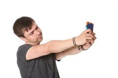 Casual young man with light beard, taking selfie on mobile phone Royalty Free Stock Image