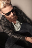 Casual young man with a long beard sitting. Angle view of a casual young man with a long beard sitting, wearing sunglasses and leather jacket, in a gray Royalty Free Stock Images
