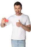 Casual young man looking at camera, keep card Royalty Free Stock Images