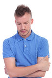 Casual young man looking worried. Picture of a young casual man looking worried at the ground and holding his hands crossed. isolated on a white background Stock Photos