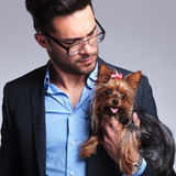 Casual young man looks at puppy. Casual young man holding a puppy and looking at it. on gray background Stock Photography