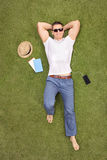 Casual young man lying in field and listening to music Royalty Free Stock Images