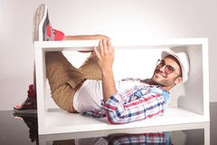 Casual young man lying inside of a white box Stock Photography