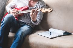 Casual young man playing guitar with notebook on sofa at home. Lifestyle Concept Stock Photos