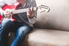 Casual young man playing guitar on sofa at home. Lifestyle Concept Royalty Free Stock Images