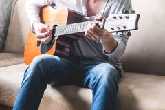 Casual young man playing guitar on sofa at home. Lifestyle Concept Royalty Free Stock Photography