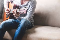 Casual young man playing guitar on sofa at home. Lifestyle Concept Stock Photo