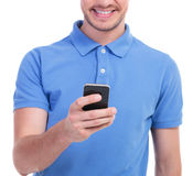 Casual young man plays on his phone Royalty Free Stock Photos