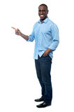 Casual young man pointing away Stock Photo