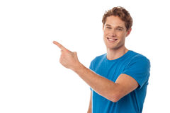 Casual young man pointing away Stock Photos