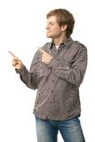 Casual young man pointing to blank space. Smiling. Copyspace, isolated on white, side view Royalty Free Stock Photo