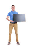 Casual young man points with chalk at blackboard Royalty Free Stock Photography