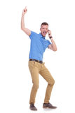 Casual young man points up while on the phone Royalty Free Stock Image