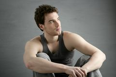 Casual young man portrait sit over gray. Grunge background Royalty Free Stock Image