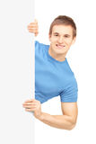 Casual young man posing behind white panel Stock Images