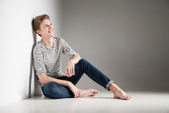 Casual young man posing on floor smiling over gray Royalty Free Stock Photos
