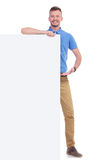 Casual young man presents board. Full length picture of a young casual man presenting a blank board and smiling for the camera. isolated on a white background Royalty Free Stock Photos